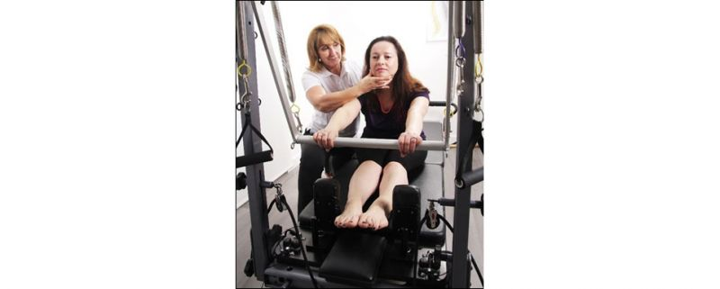 Jane Collins working with a patient on the Reformer