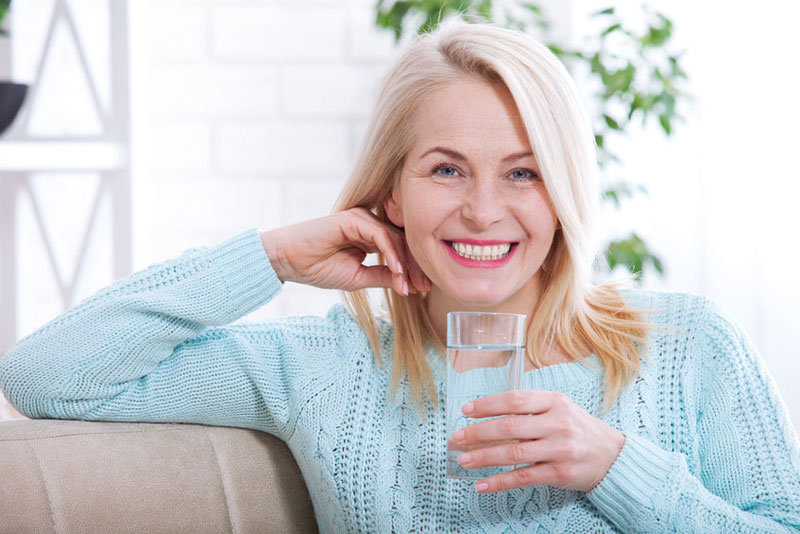Mature older woman drinking a glass of water enhancing her immunity