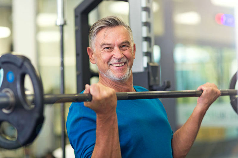 Mature man holding a heavy weight above his chest in the gym