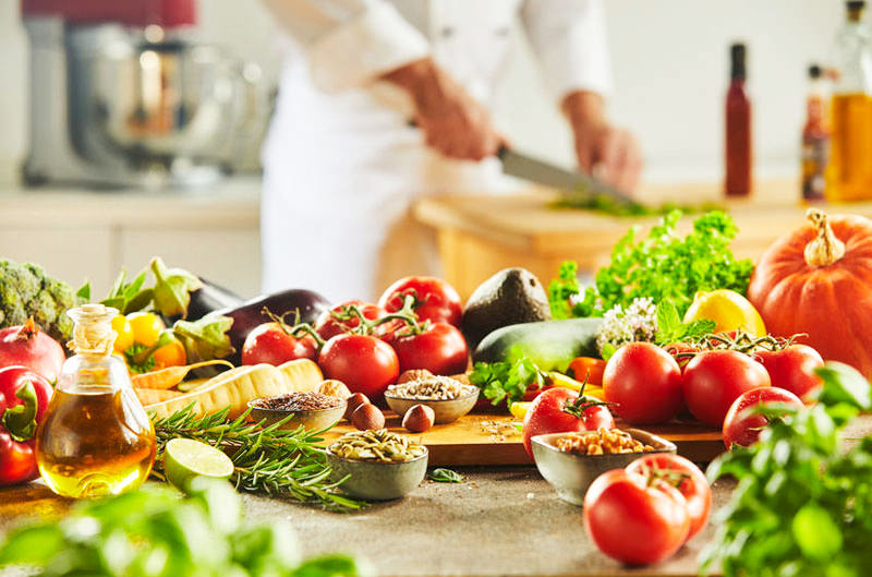 Display of food suitable for a Mediterranean diet with a chef in the background preparing the food